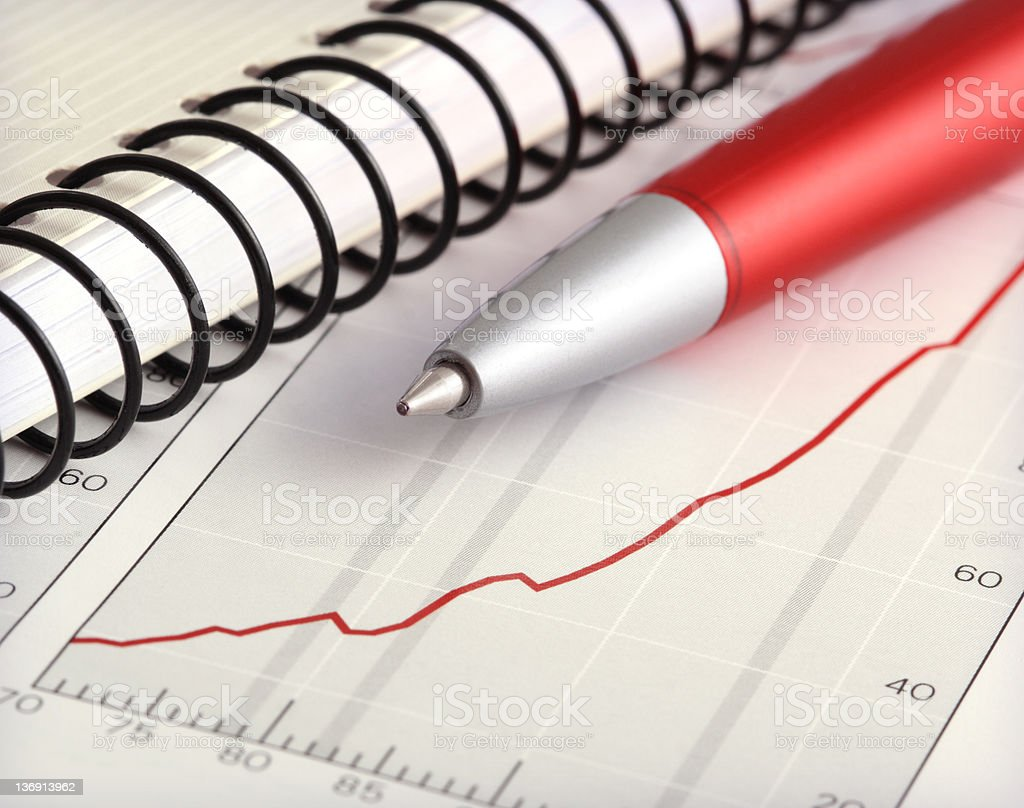 Positive Earning Chart with Pen and Notebook royalty-free stock photo