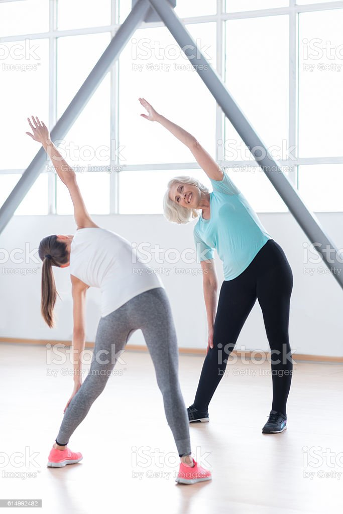 Positive enthusiastic woman doing bending exercises stock photo