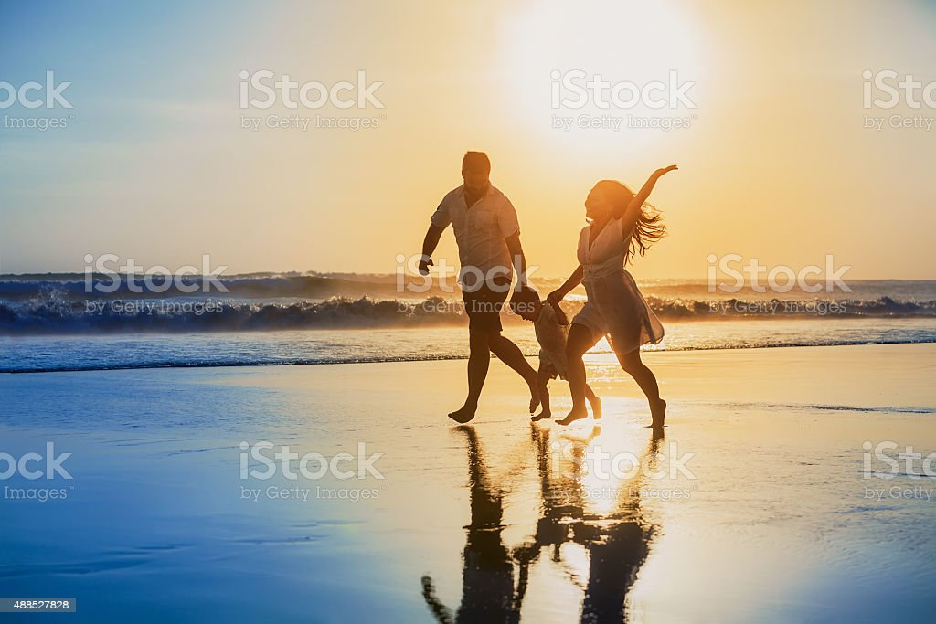 Positive family running with fun on the sunset beach stock photo
