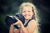 positive female child taking pictures with camera in park