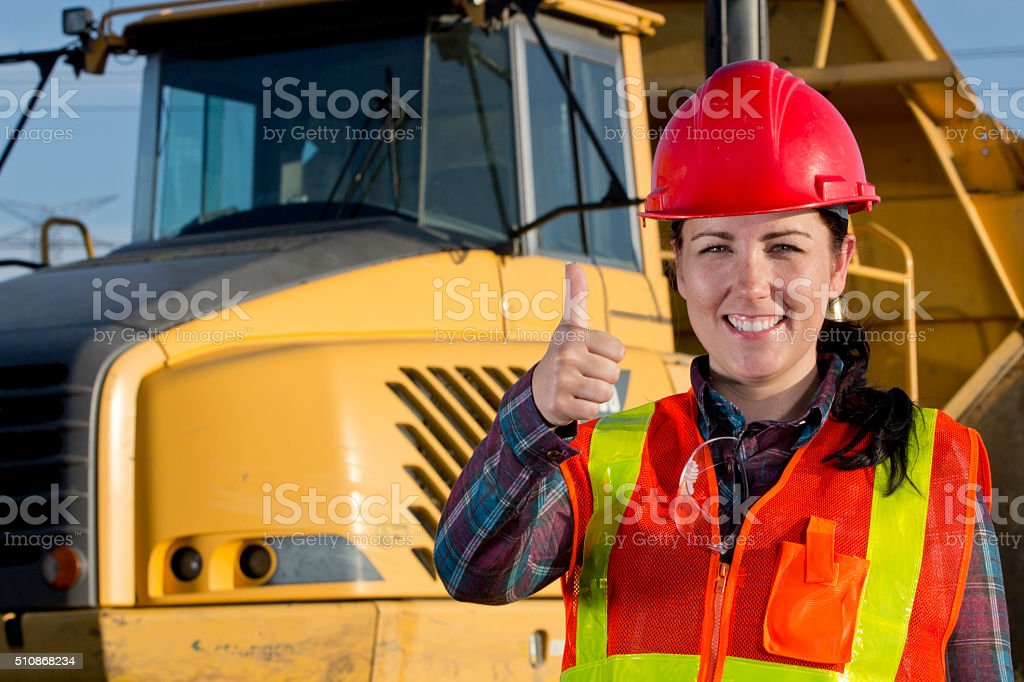 Positive Female Construction Worker and Heavy Hauling Truck stock photo