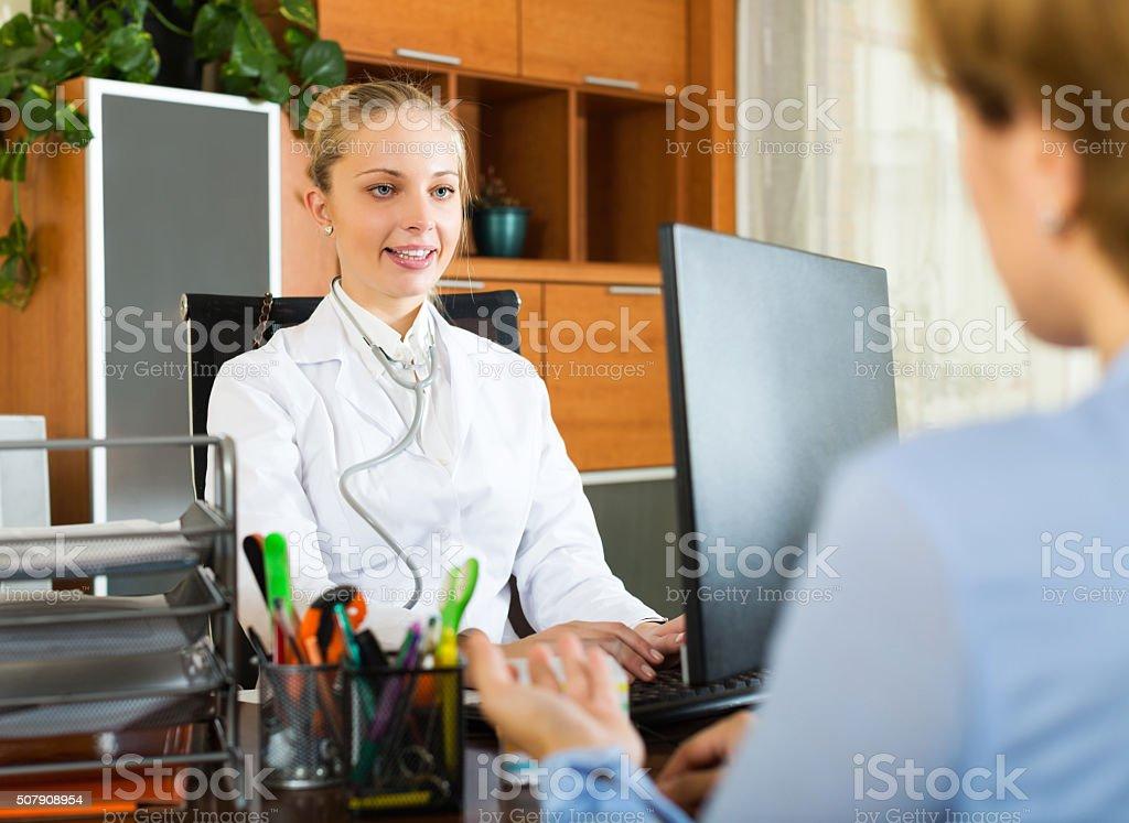 Positive female doctor discharging patient stock photo