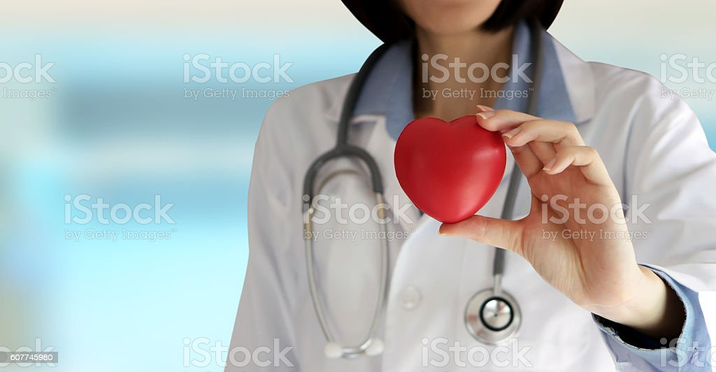 Positive female doctor standing with stethoscope and red heart s stock photo