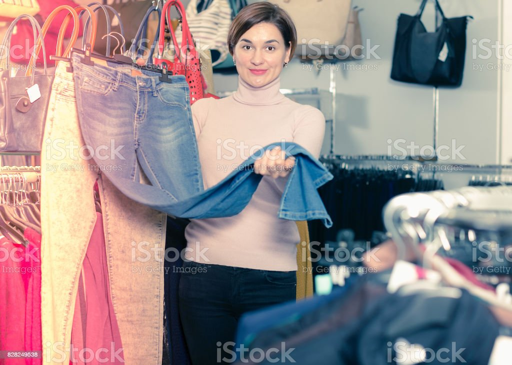 Positive girl deciding on new jeans stock photo