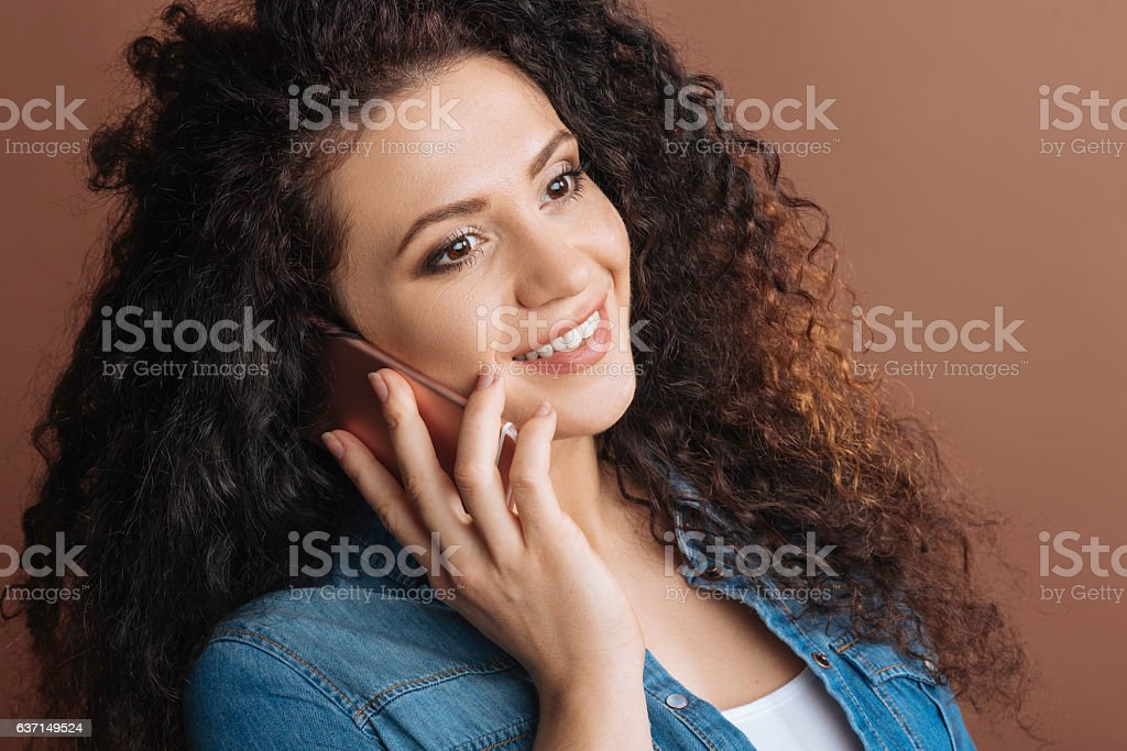 Positive girl having conversation on phone stock photo