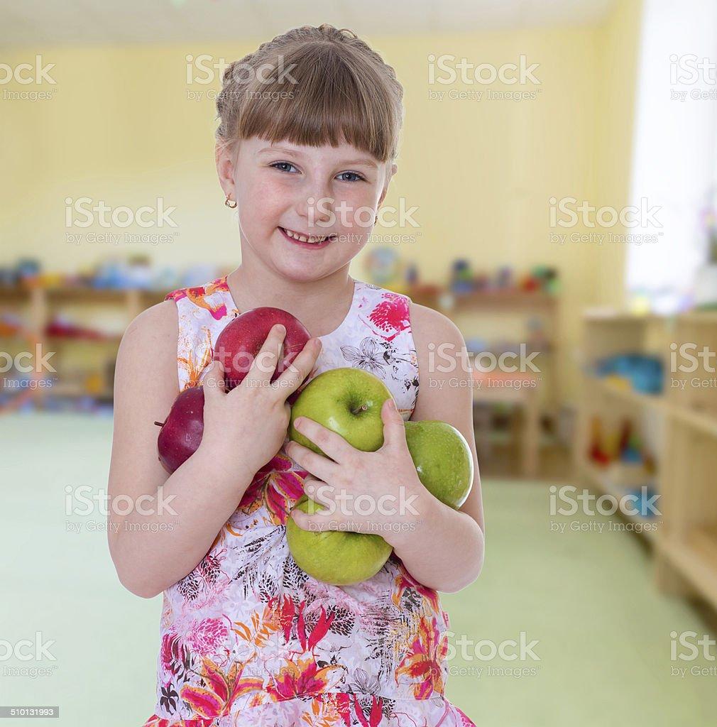 positive jeune fille tenant un tas de pommes. photo libre de droits