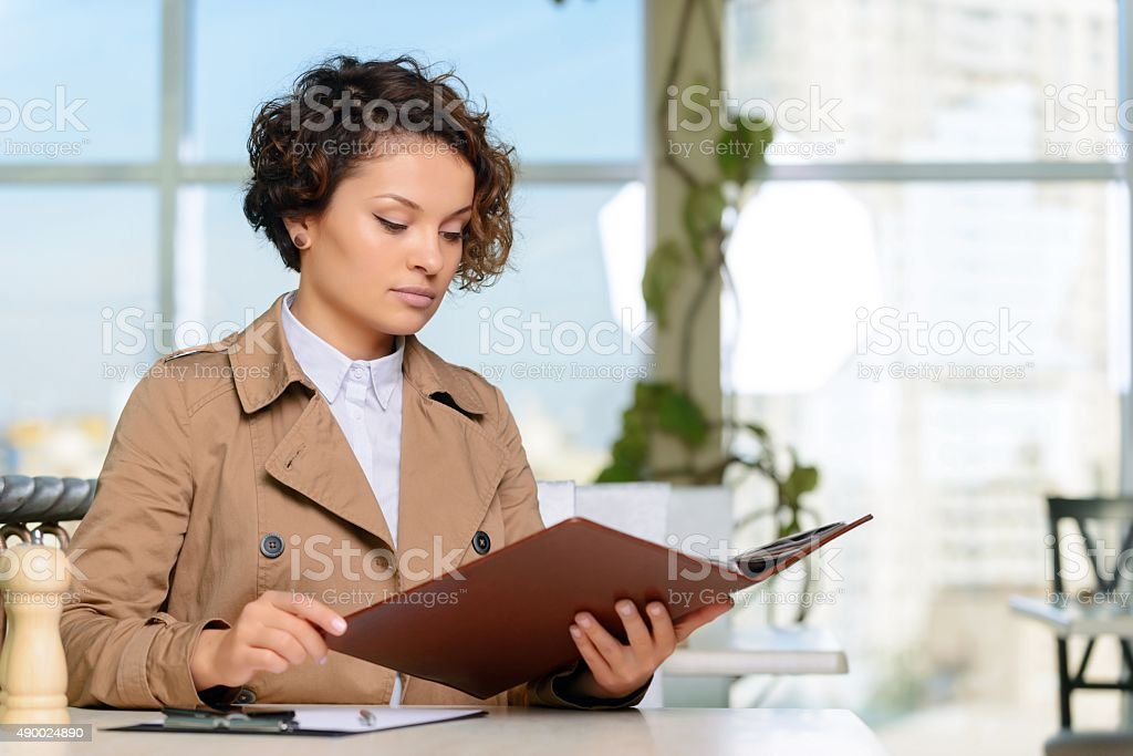 Positive girl sitting at the table stock photo