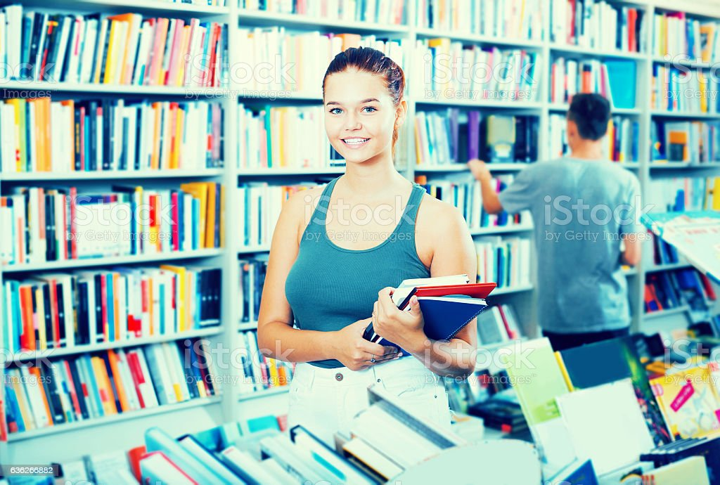 Positive girl teenager holding new books in hands stock photo