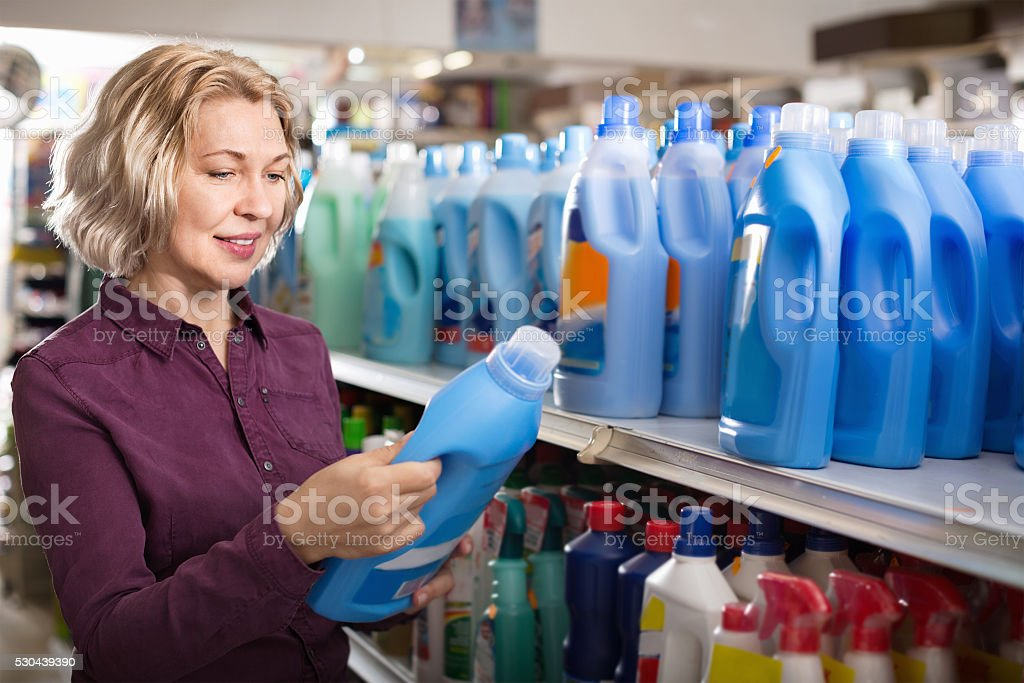 Positive glad female with selecting fabric conditioner stock photo