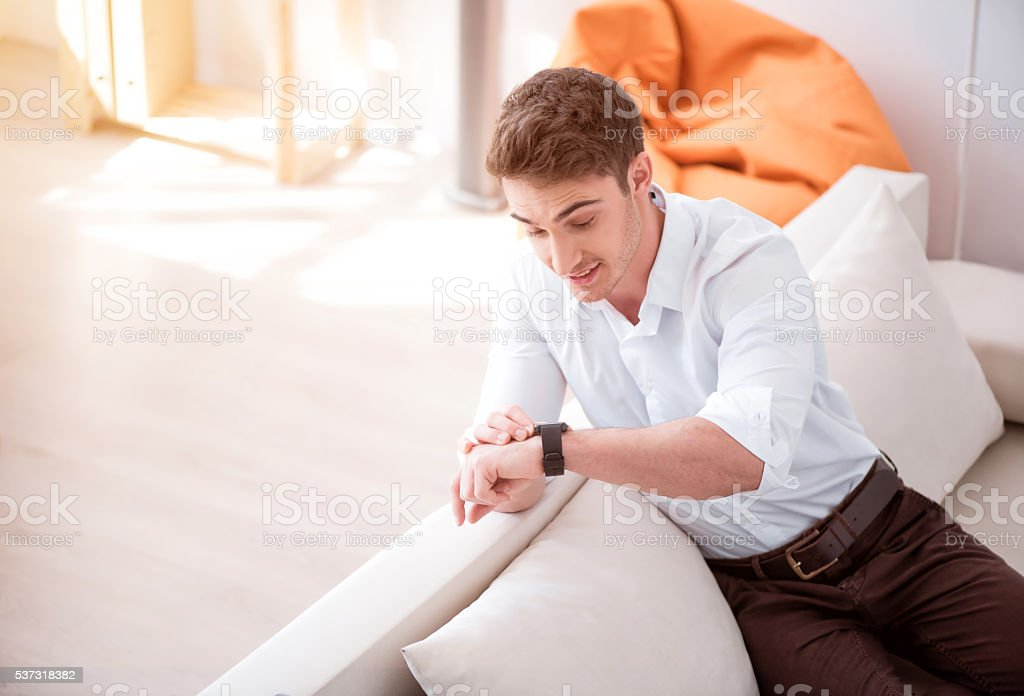 Positive handsome man sitting on the couch stock photo