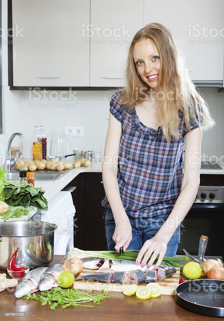 Positive housewife cooking saltwater fish stock photo