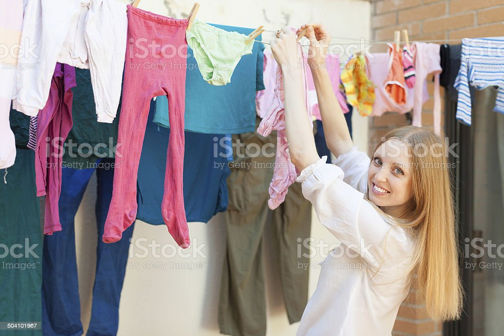 Positive long-haired girl drying clothes on clothes-line stock photo