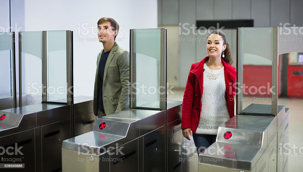 Positive man and woman posing at baffle gate stock photo