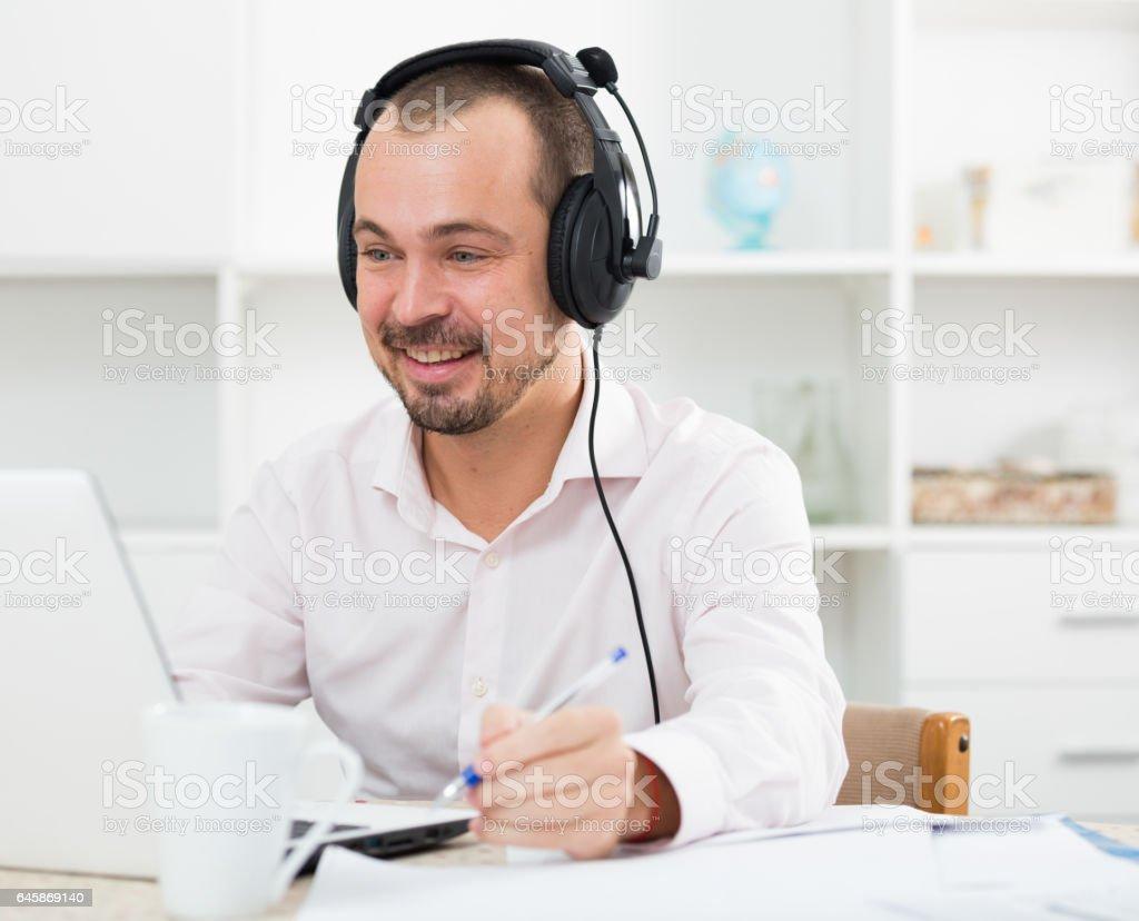 Positive man in headphones near computer stock photo