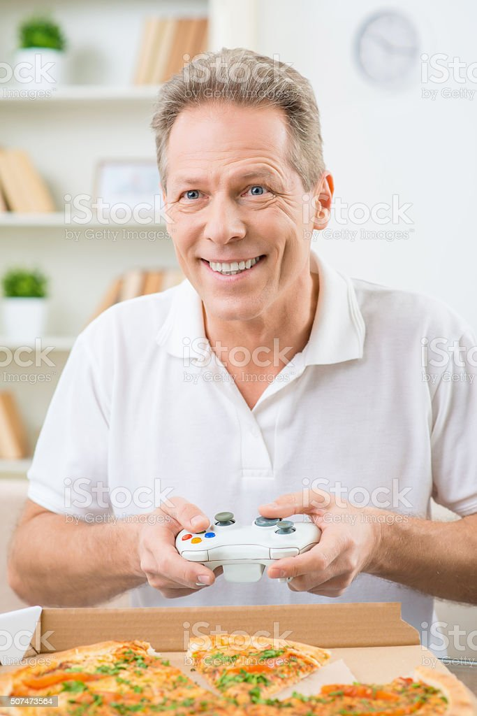 Positive man playing video game stock photo