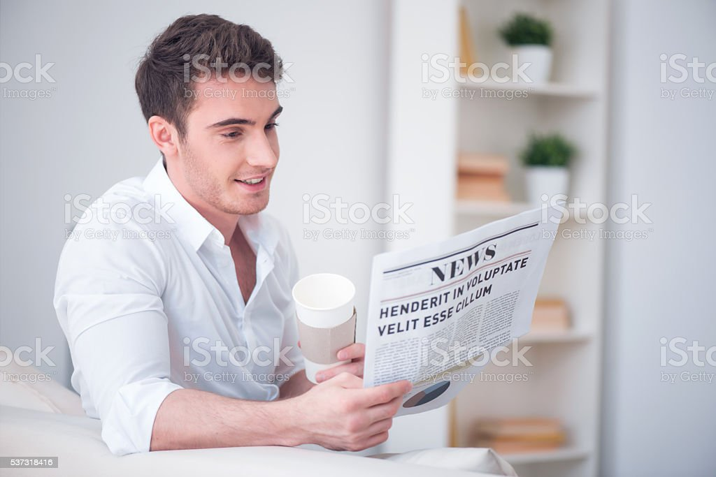 Positive man reading newspaper. stock photo