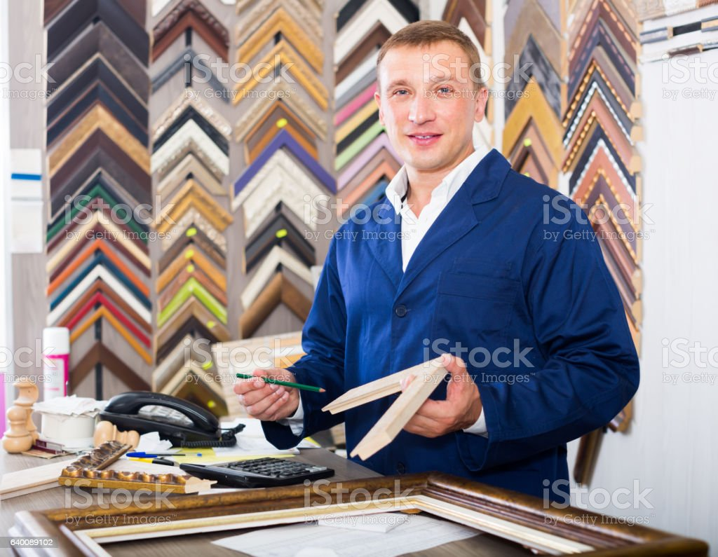 positive man seller in picture framing studio with wooden detail stock photo