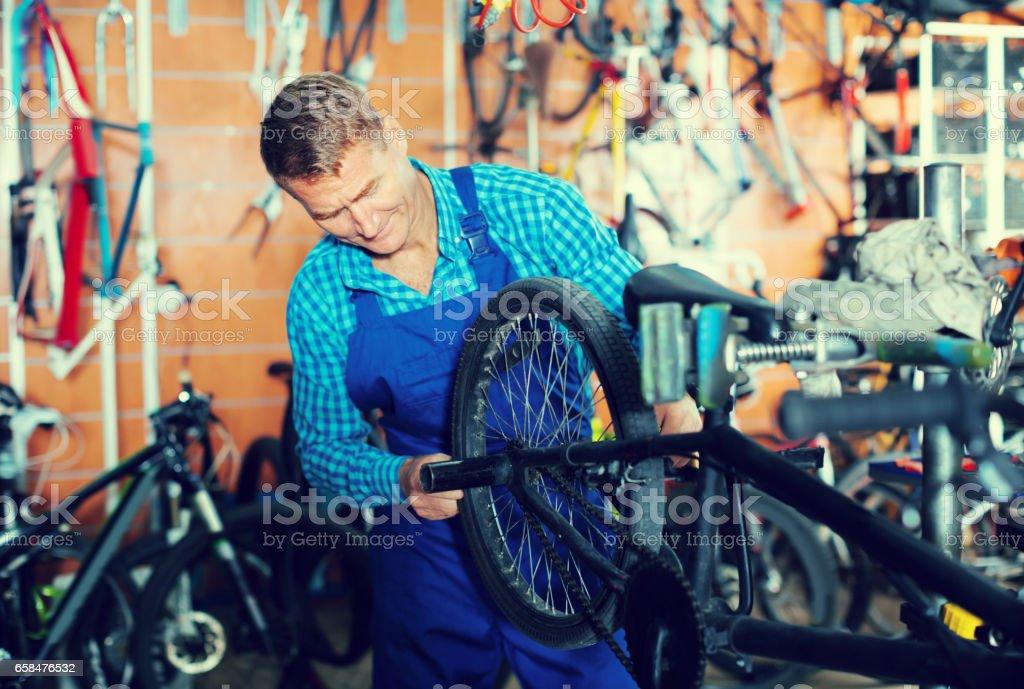 Positive man seller wearing uniform fixing bike stock photo