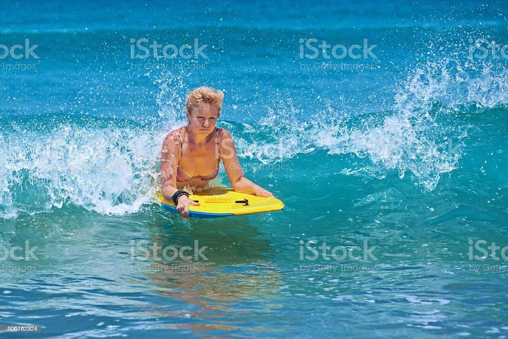 Positive mature woman surfing with fun on ocean waves stock photo