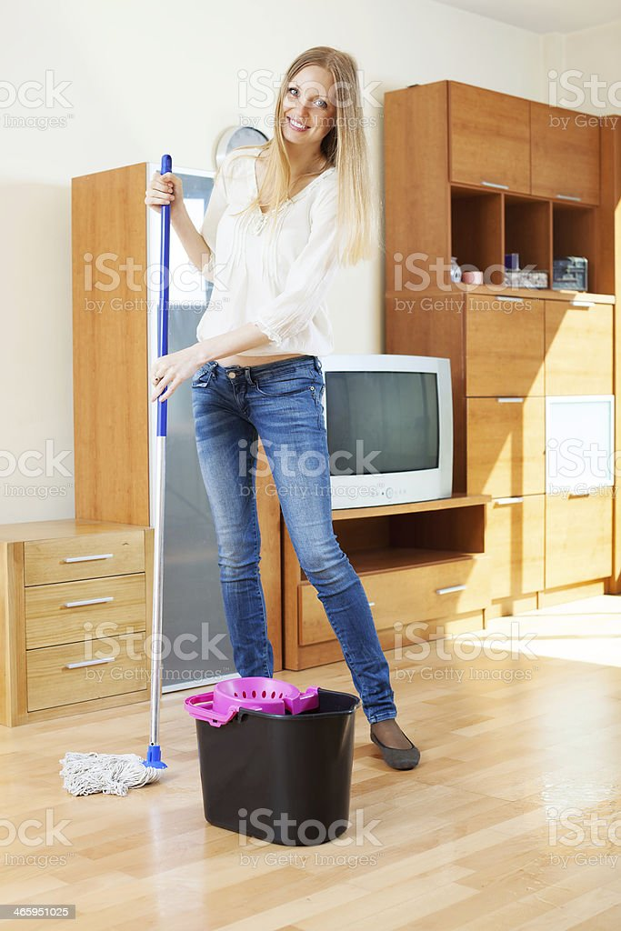 Positive ordinary housewife washing parquet stock photo