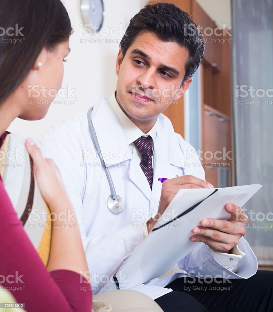 Positive physician consulting sick woman in domestic interior stock photo