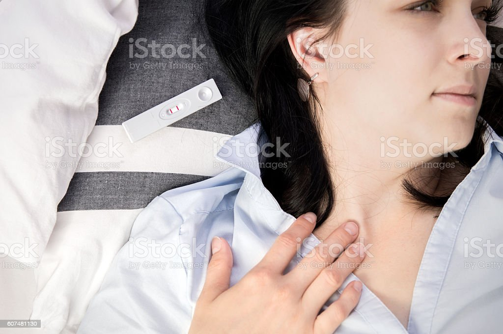 Positive pregnancy test lying on bed. stock photo