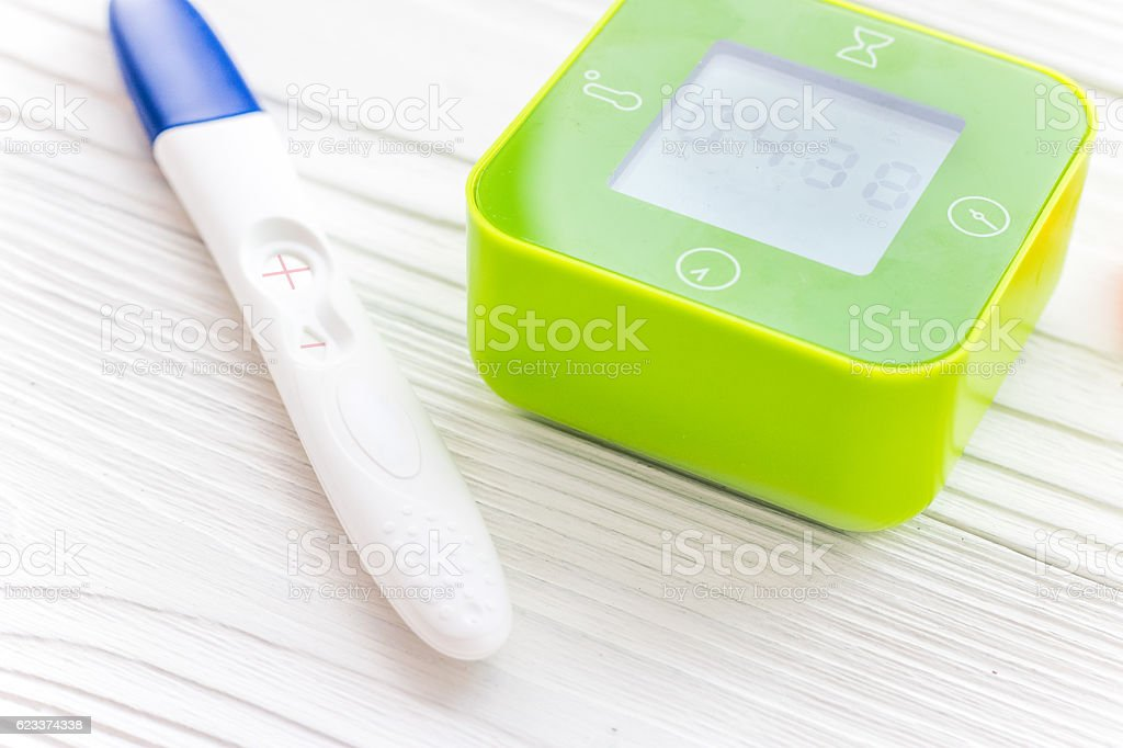 Positive pregnancy test with heart on wooden background stock photo