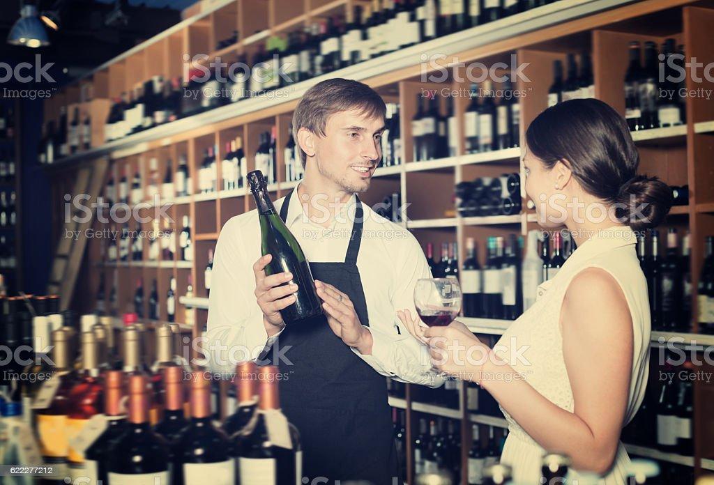 Positive seller man giving sample taste of wine stock photo