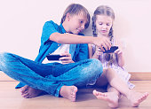 Positive siblings playing with phones