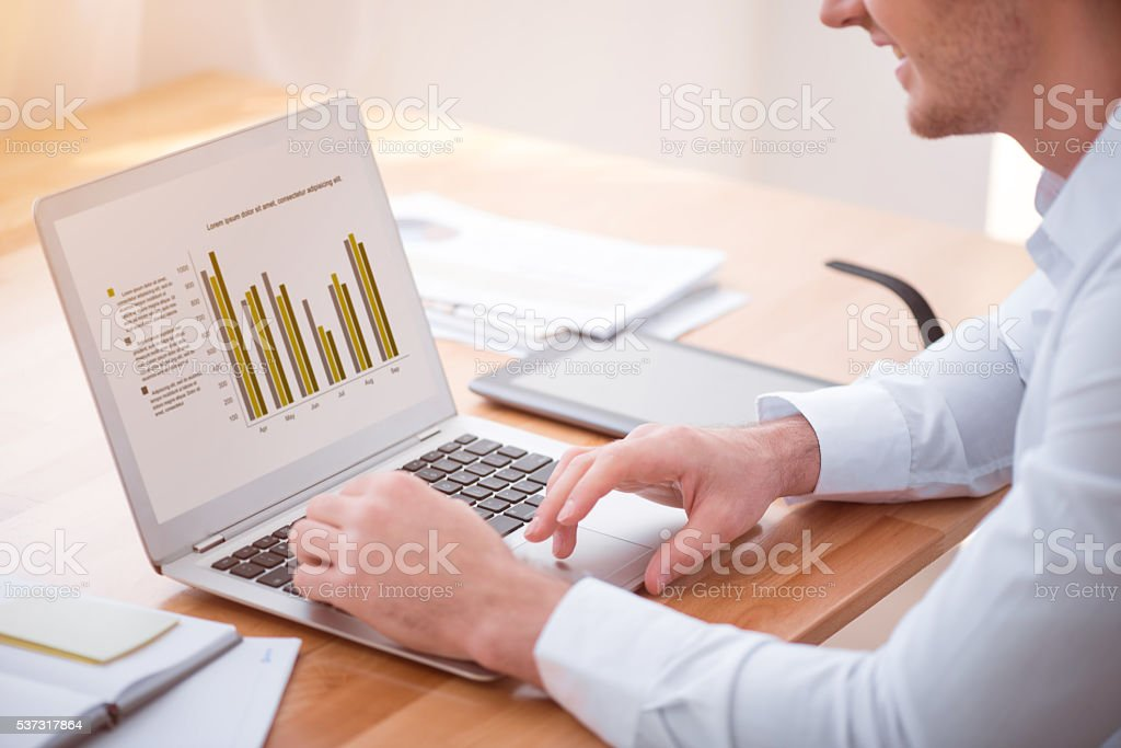 Positive smiling man working on the laptop stock photo