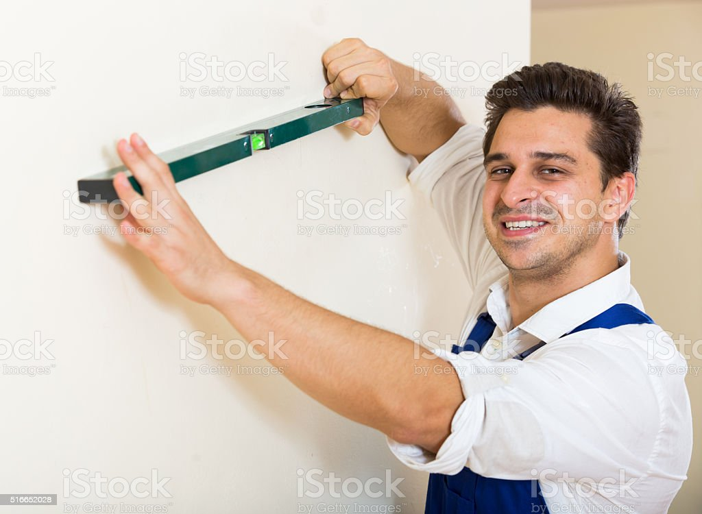 Positive specialist making wall plane in new building stock photo