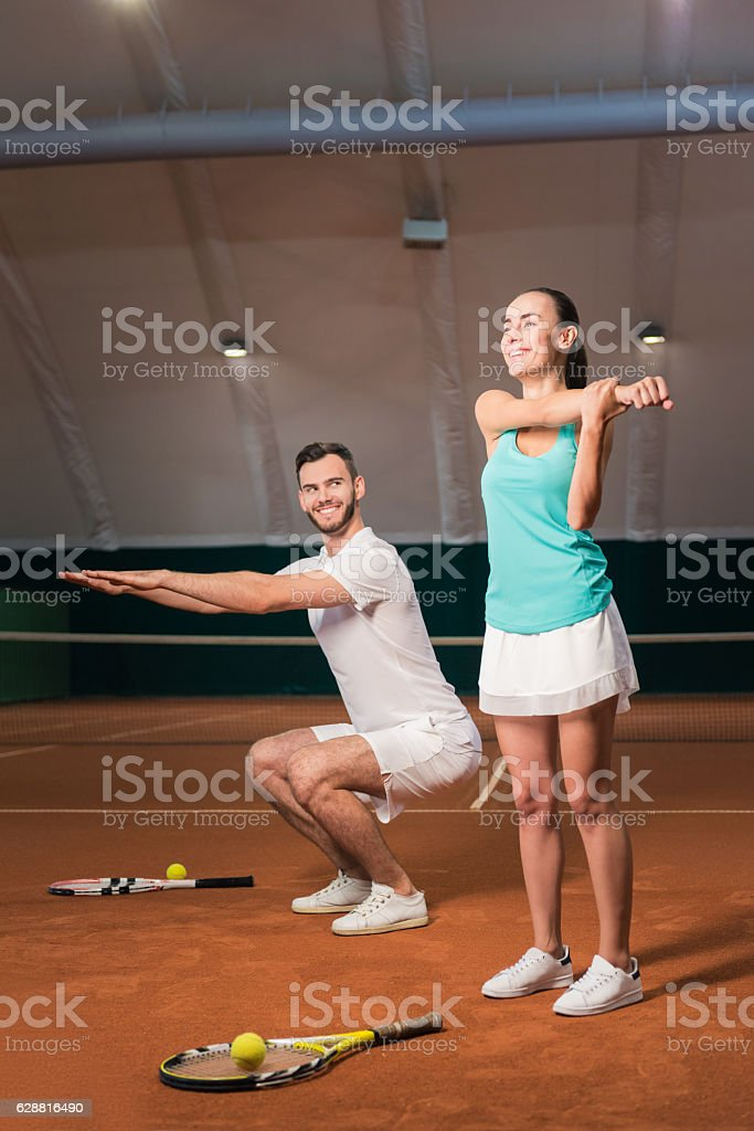 Positive tennis players doing sport exercises stock photo