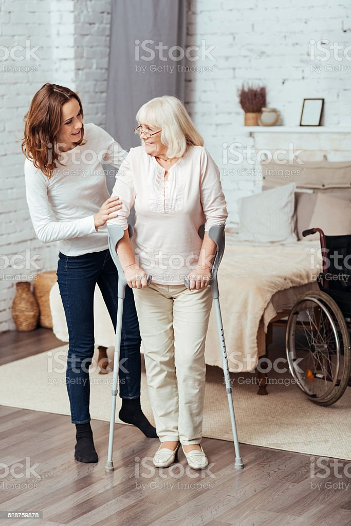 Positive woman helping he grandmother to walk with crutches stock photo