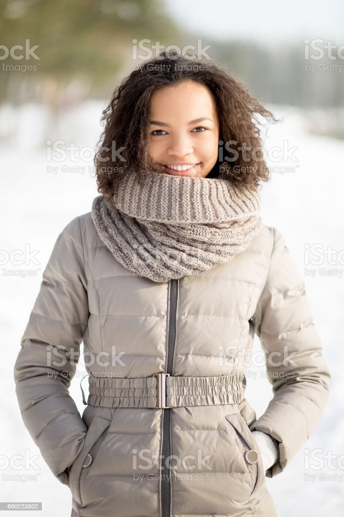 Positive woman in warm jacket standing in forest stock photo