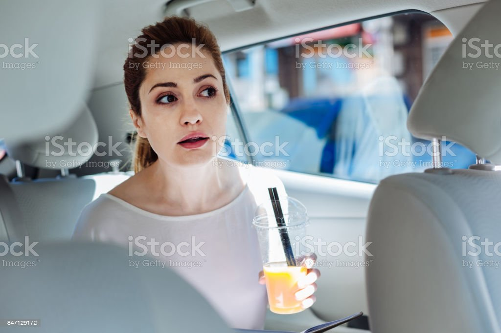 Positive young businesswoman holding a cup with juice stock photo