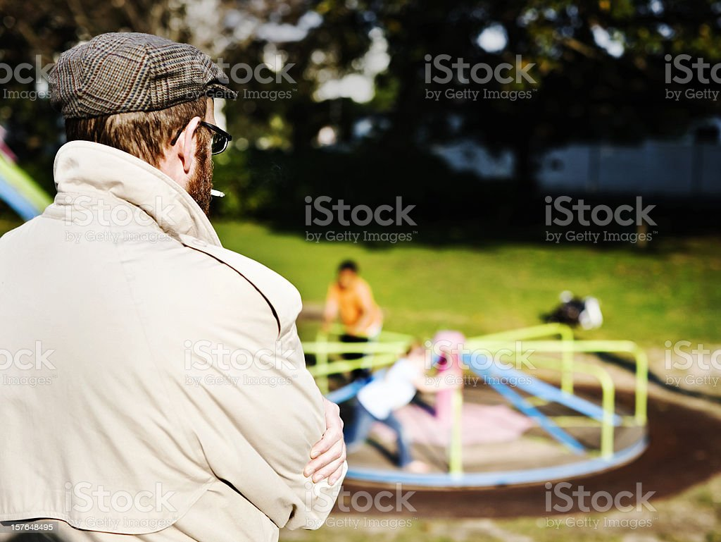 Possible pedophile watches kids play in park stock photo