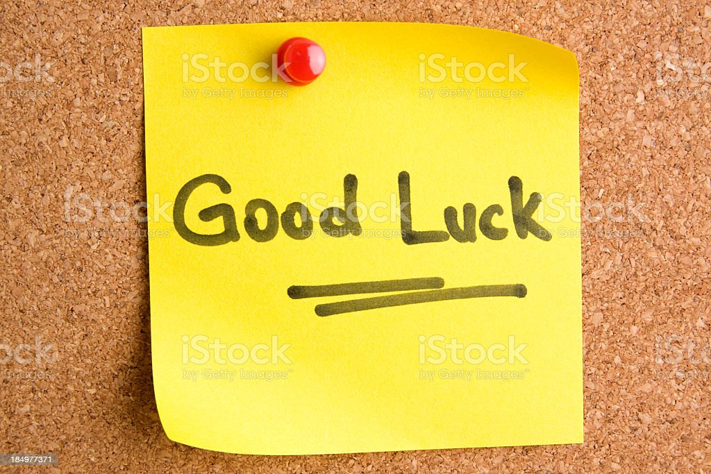 A post it note saying Good Luck with a red pin stock photo