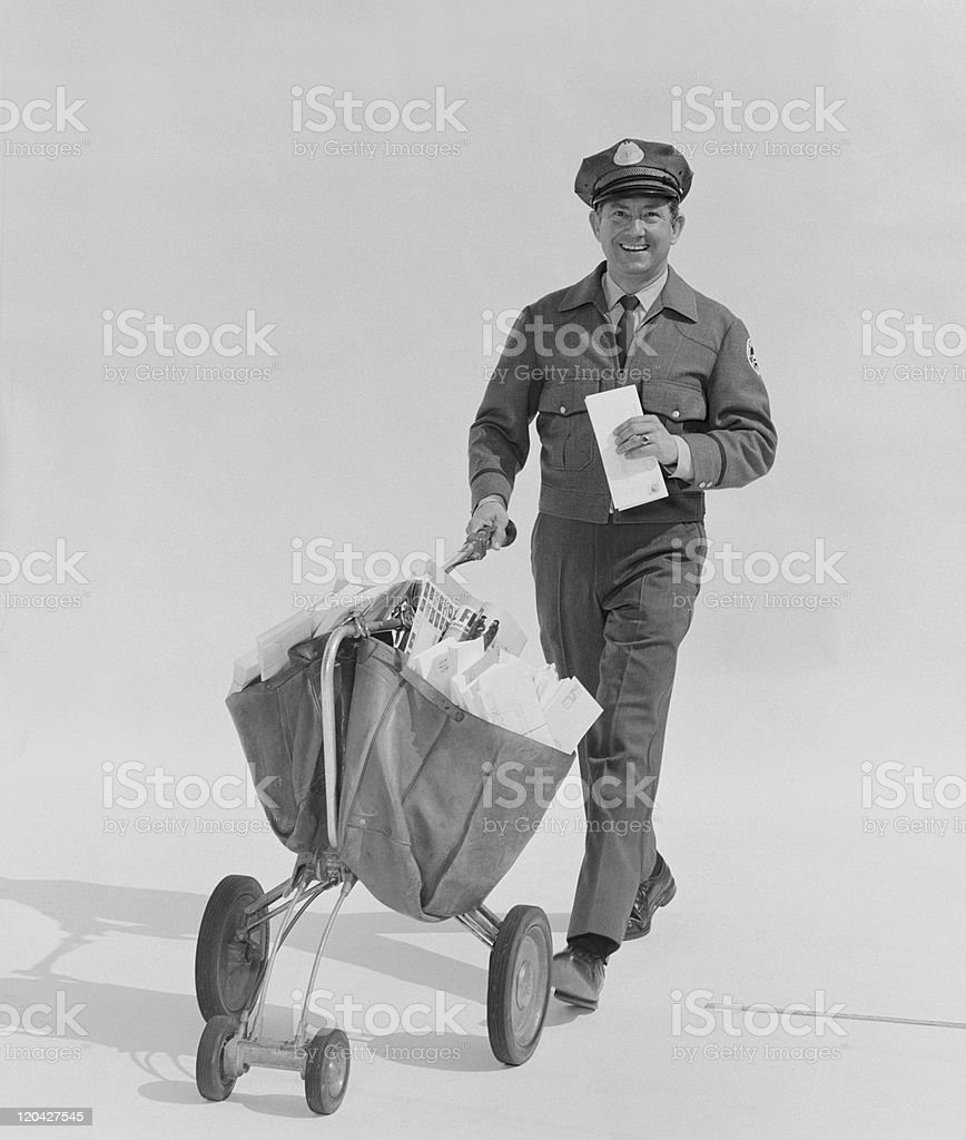 Postal worker carrying letters on wheel barrow against white background, portrait stock photo