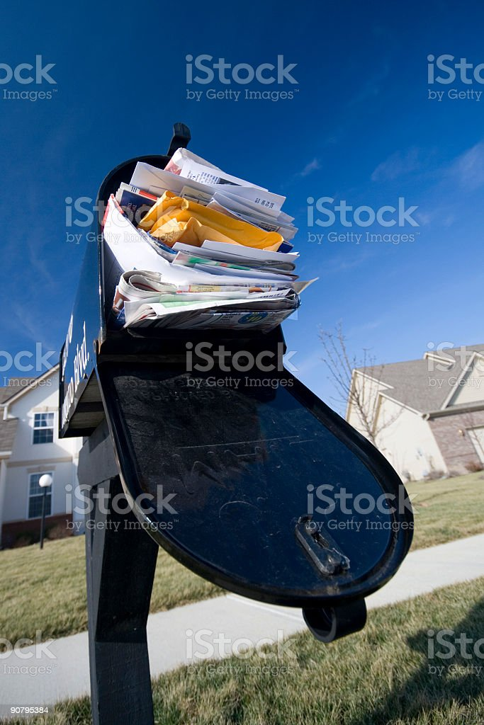 A postbox stuffed with junk mail and the door hanging open stock photo