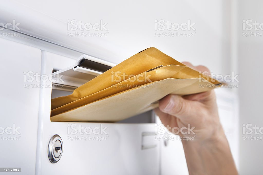 Postman Putting Letters In Mailbox stock photo