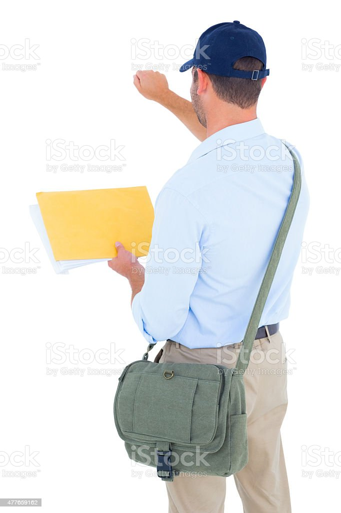 Postman with letter knocking on white background stock photo