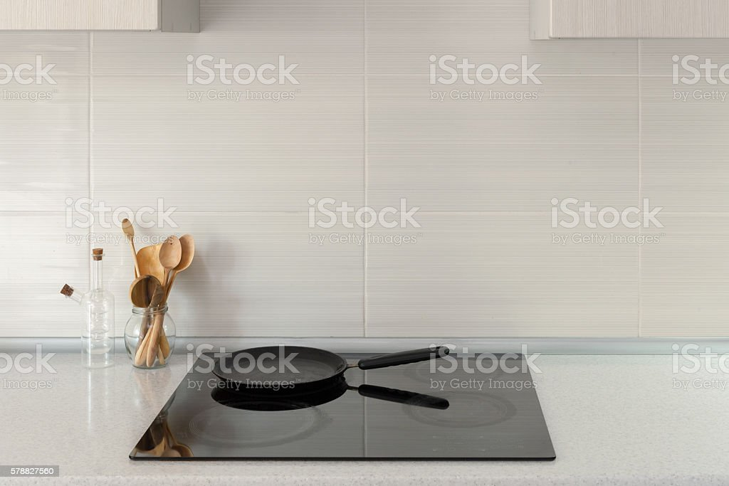 Pot and wooden spoons in modern kitchen with induction stove stock photo