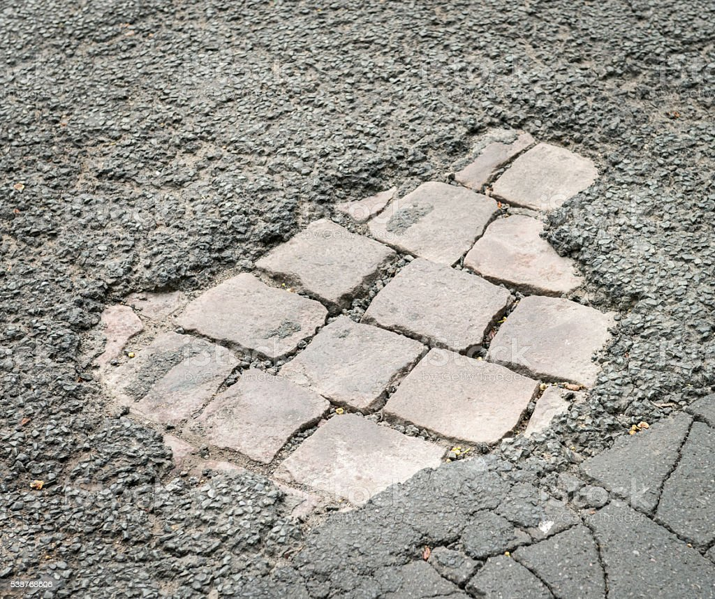 Pot hole in the road surface revealing cobbles below stock photo