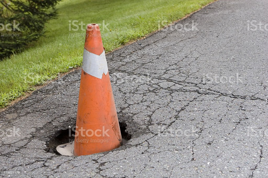 Pot hole in the road with an orange cone inside stock photo