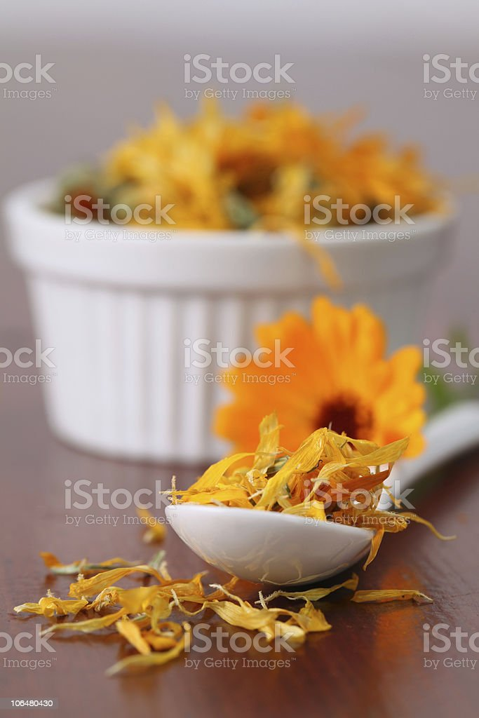 Pot marigold tea leaves in a white spoon and ramekin royalty-free stock photo