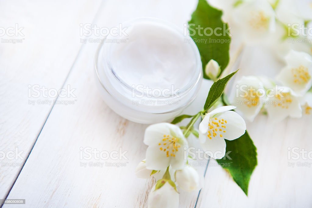 Pot of beauty cream with flower on white wooden table stock photo