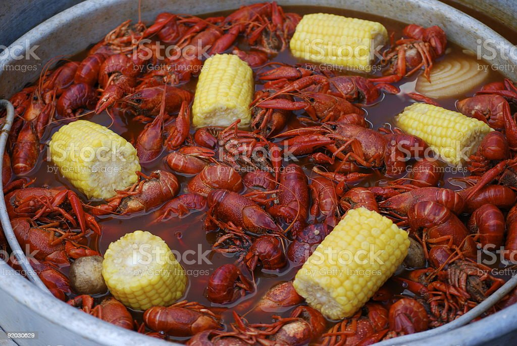 Pot of boiled crawfish with corn, potatoes, and onions stock photo
