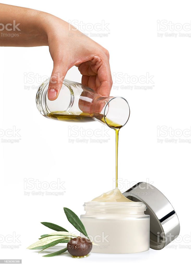 A pot of face cream having olive oil poured into it royalty-free stock photo