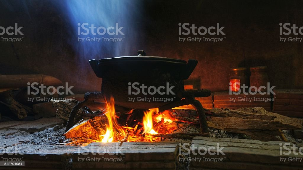 Pot of food on burning wood fire. stock photo