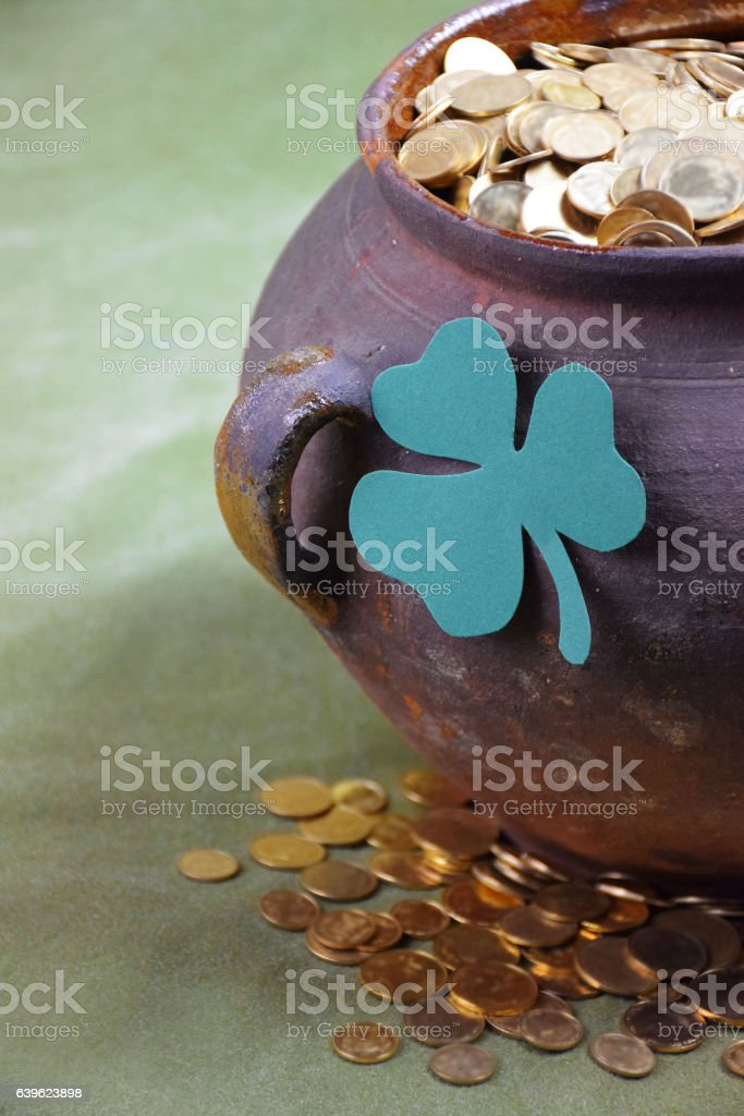 Pot of gold and a shamrock leaf. Close-up. stock photo